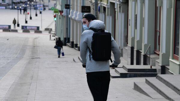 Молодой человек в защитной маске на самокате на улице Кузнецкий мост в Москве