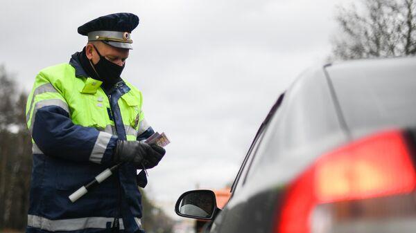 Инспектор дорожно-патрульной службы проверяет у водителя цифровой пропуск на передвижение