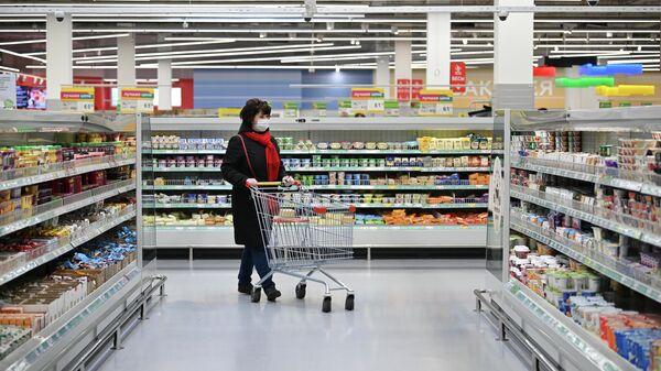 Женщина в защитной маске в гипермаркете