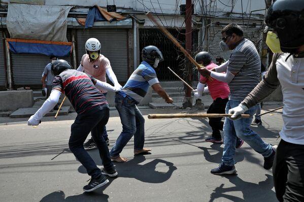 Полицейские в штатском ловят человека, нарушившего карантин в Ховре на окраине Калькутты, Индия. 19 апреля 2020 года