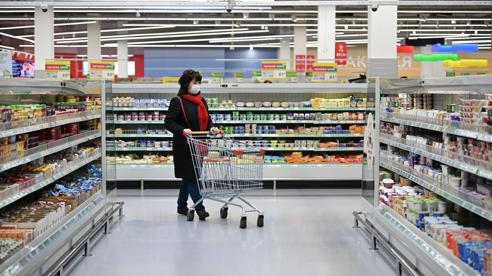 Женщина в защитной маске покупает продукты в гипермаркете - РИА Новости, 1920, 13.10.2020