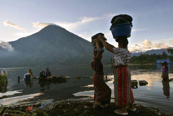 Женщины стирают одежду в озере Атитлан у подножия вулкана Сан-Педро, Гватемала