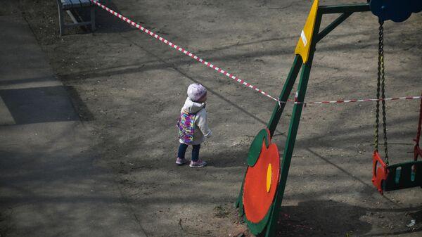 Ребенок на детской площадке во дворе на одной из улиц в Москве