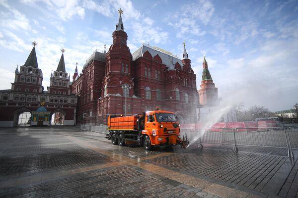 Автомобиль коммунальных служб дезинфицирует дороги и тротуары в центре Москвы.
