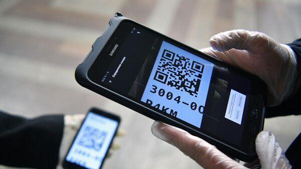 Проверка цифровых пропусков у пассажиров во время рейда сотрудниками полиции по выявлению нарушений социальной дистанции в 1,5 м в общественном транспорте