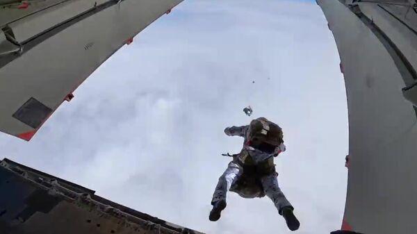 Российские десантники совершают групповое десантирование с самолета Ил-76 на новых парашютных системах с высоты 10 000 метров в экстремальных условиях Арктики в районе архипелага Земля Франца Иосифа. Стоп-кадр видео