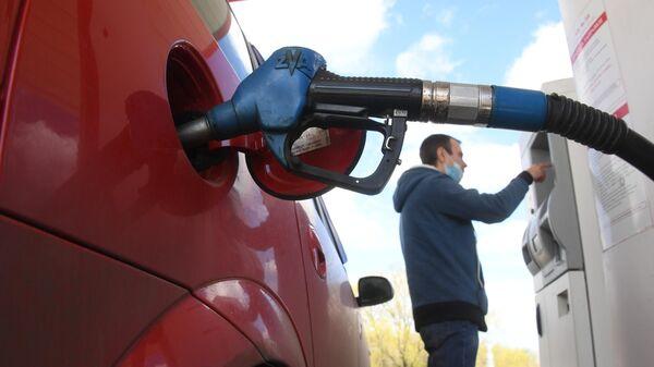Мужчина оплачивает автомобильное топливо на АЗС