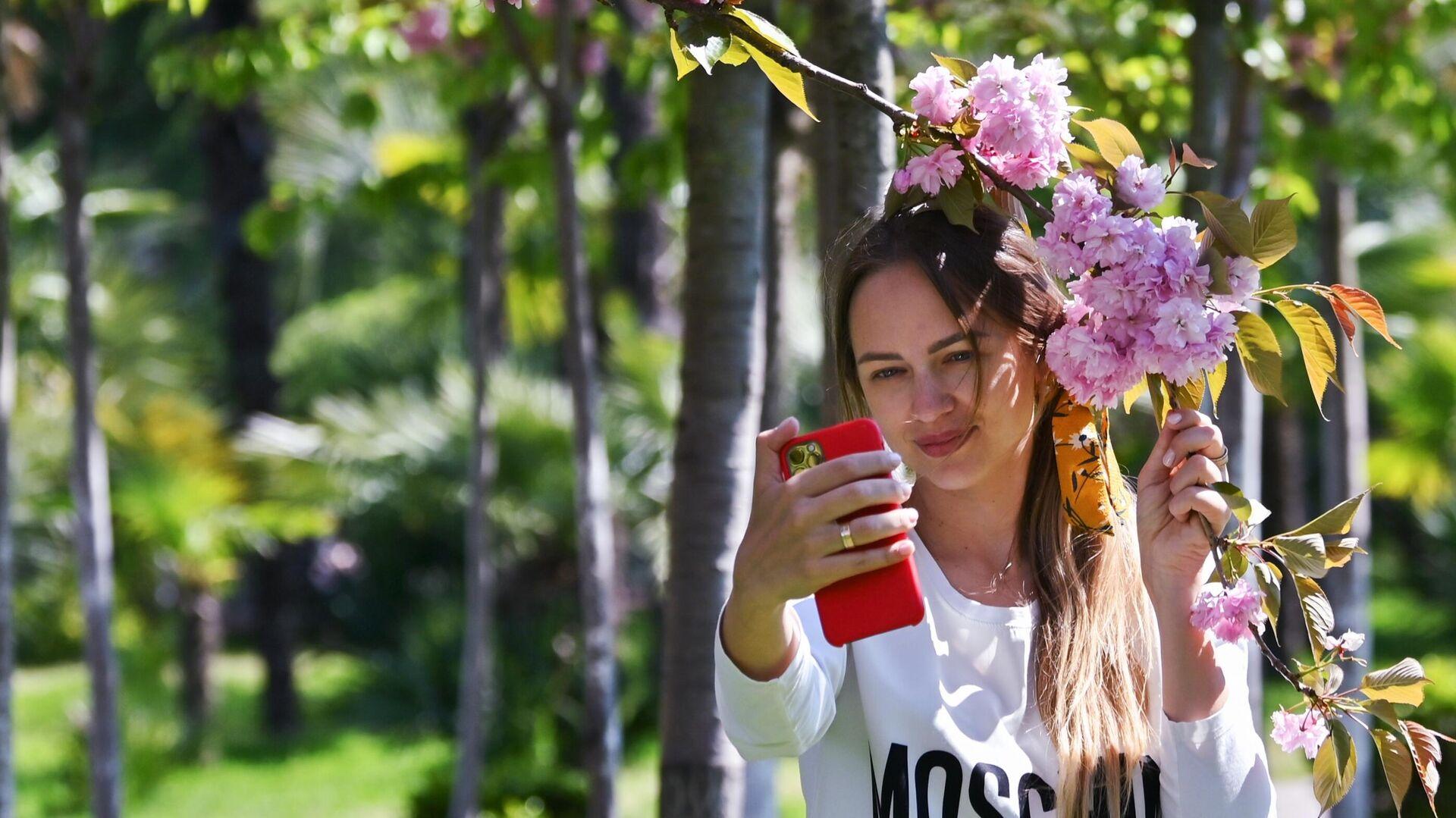 Девушка фотографируется на мобильный телефон на аллее Черешневый сад в Сочи - РИА Новости, 1920, 08.06.2020