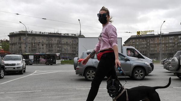 Девушка в защитной маске с собакой на улице Новосибирска
