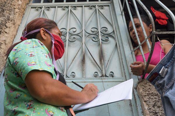 Медицинский работник во время обхода жителей для выявления случаев заболевания коронавирусом в фавелах Каракаса