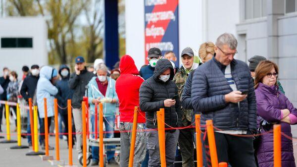 Люди в очереди в строительный гипермаркета Бауцентр в Калининграде