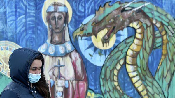Женщина проходит мимо граффити в Киеве