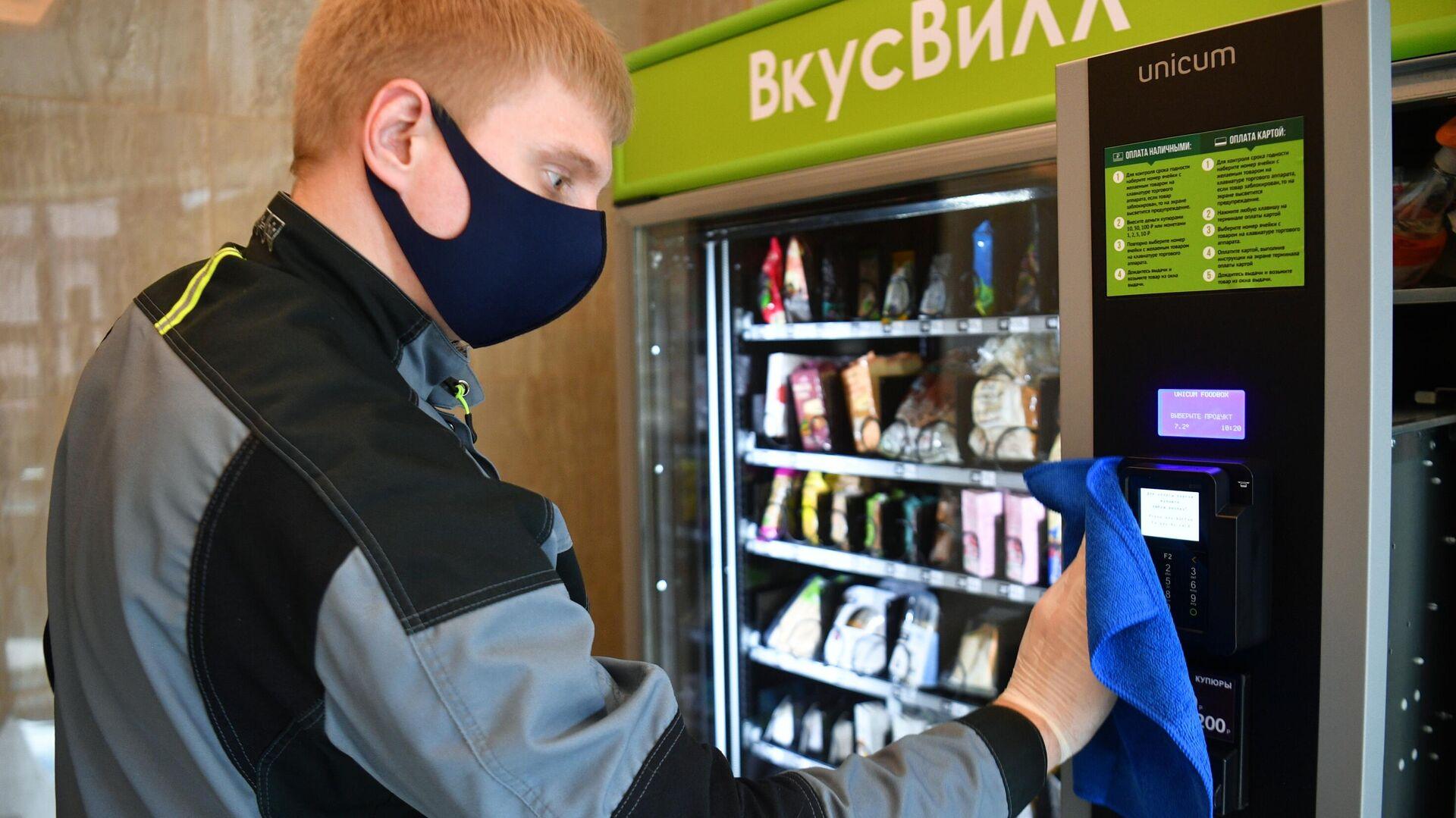 Сотрудник сетевого магазина продуктов питания ВкусВилл проводит санитарную обработку вендингового автомата - РИА Новости, 1920, 03.08.2021