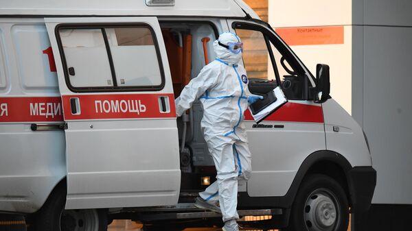Медик выходит из машины скорой медицинской помощи, доставившей пациента в карантинный центр в Коммунарке