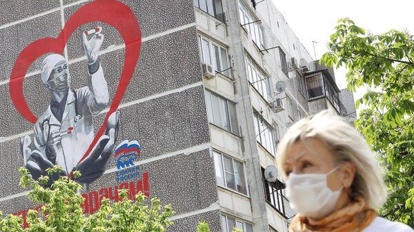 Женщина в медицинской маске около дома с авторским граффити художника Евгения Аморфиса с надписью Спасибо врачам улице 1 мая в Краснодаре