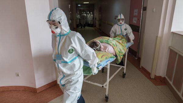 Медицинские работники везут пациента в стационаре для больных с коронавирусной инфекцией