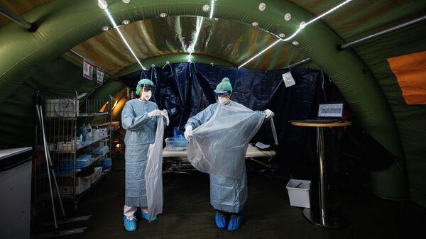 Медицинские работники надевают средства индивидуальной защиты в палатке для тестирования на коронавирус COVID-19 в Стокгольме, Швеция