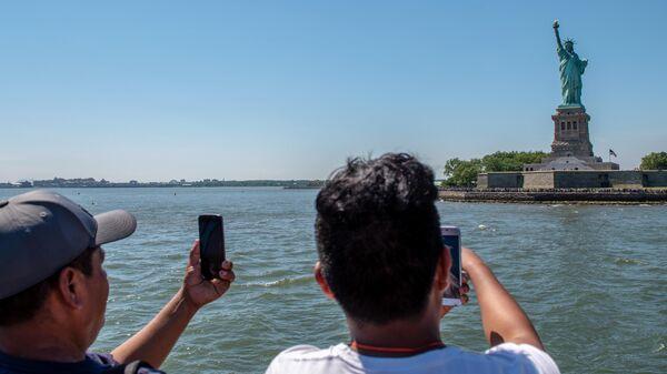 Туристы фотографируют статую Свободы в Нью-Йорке