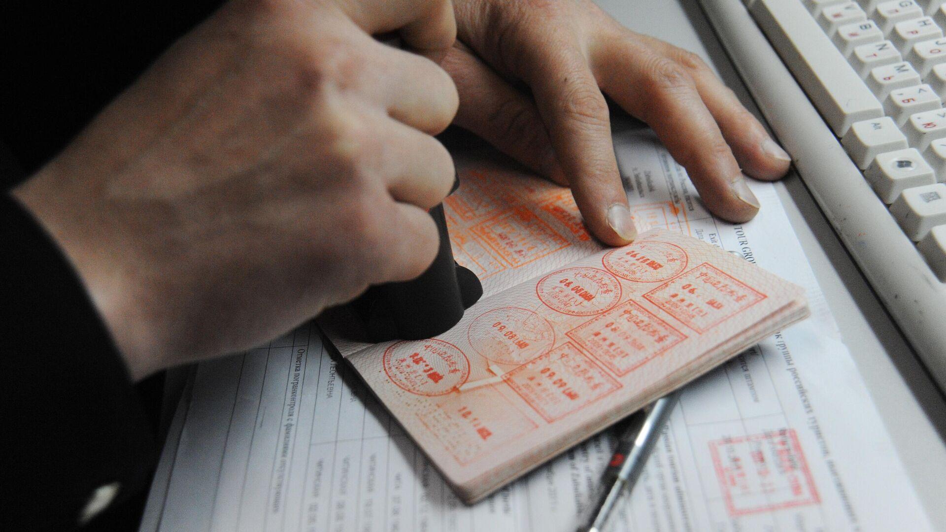 Печати в паспорте гражданина, проходящего пограничный контроль на автомобильном пункте пропуска на российско-китайской границе между городами Забайльском и Маньчжурией - РИА Новости, 1920, 05.11.2020