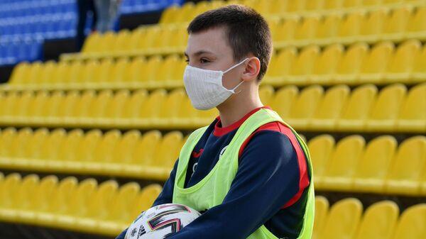 Сотрудник, подающий мячи, в защитной маске во время футбольного матча