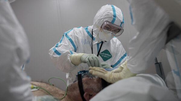 Врачи и пациент в отделении реанимации и интенсивной терапии госпиталя для зараженных коронавирусной инфекцией COVID-19 в центре МГУ имени М. В. Ломоносова