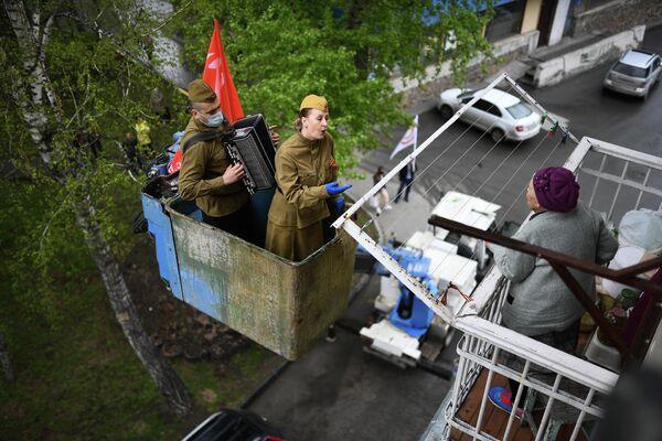 Гармонист и солистка поздравляют ветерана Великой Отечественной войны Татьяну Прокопьевну Белесову с наступающим днем Победы в Новосибирске