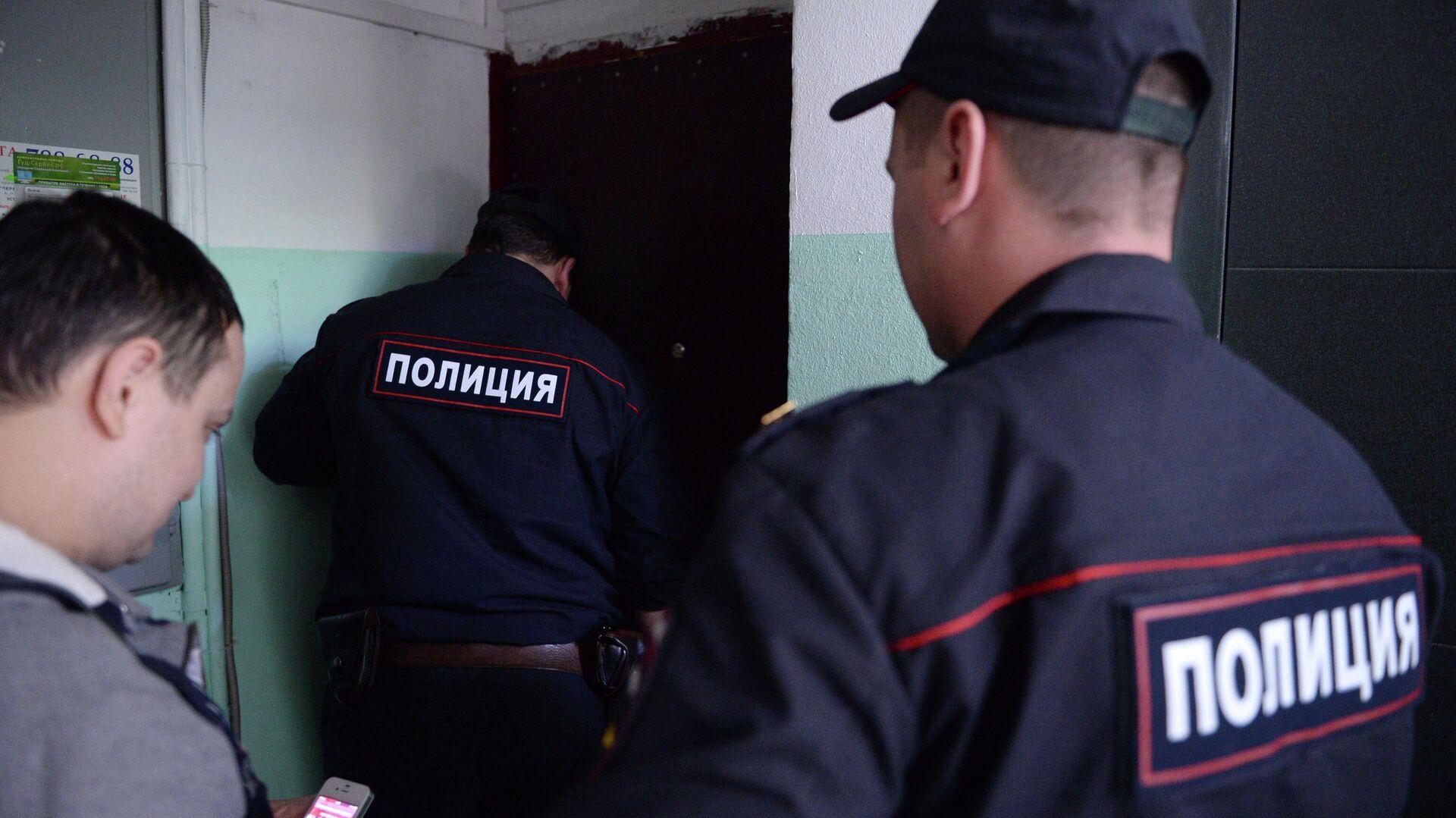 Сотрудники полиции стоят у двери квартиры в жилом доме - РИА Новости, 1920, 03.10.2020