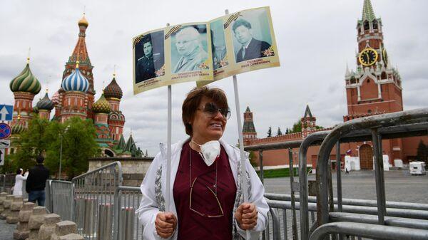 Женщина участвует в акции Бессмертный полк на Красной площади в Москве