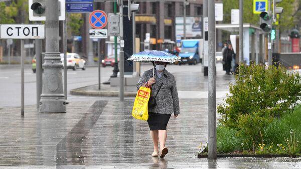 Женщина под зонтом на улице Зацепский Вал в Москве