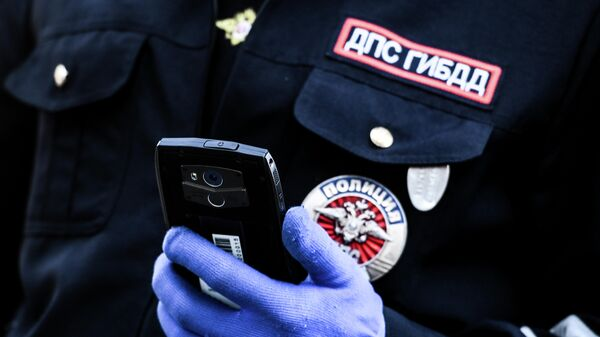 Сотрудник дорожно-патрульной службы ГИБДД во время проверки наличия пропуска у водителя на блокпосту в Москве