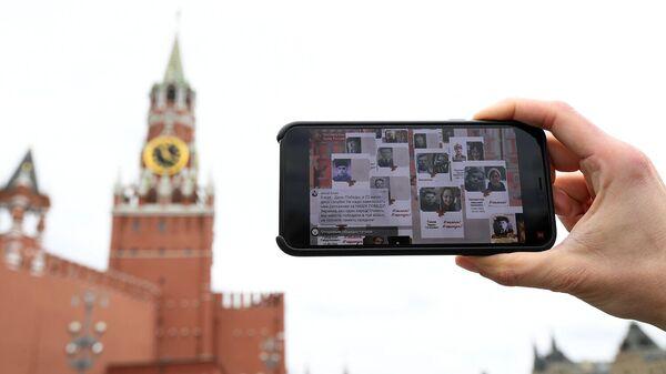 Молодой человек смотрит трансляцию акции Бессмертный полк на Васильевском спуске в Москве