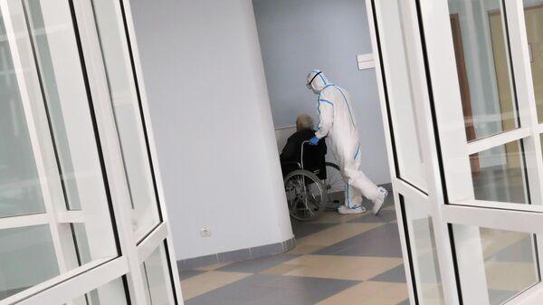 Медицинский работник и пациент в стационаре для больных с коронавирусной инфекцией