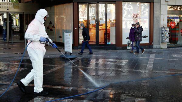 Мужчина дезинфицирует улицу перед открытием магазинов в Брюсселе, Бельгия