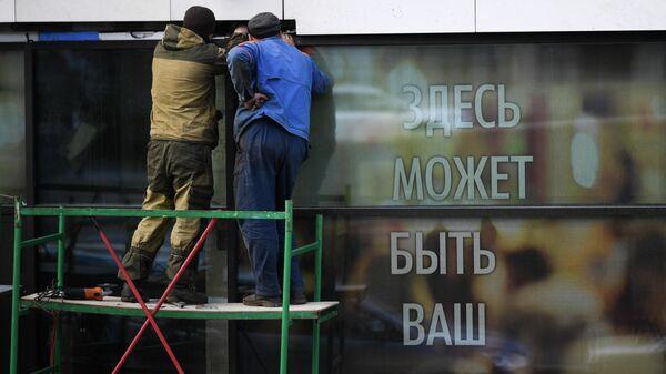 Мужчины ремонтируют витрину магазина в Москве во время режима самоизоляции жителей