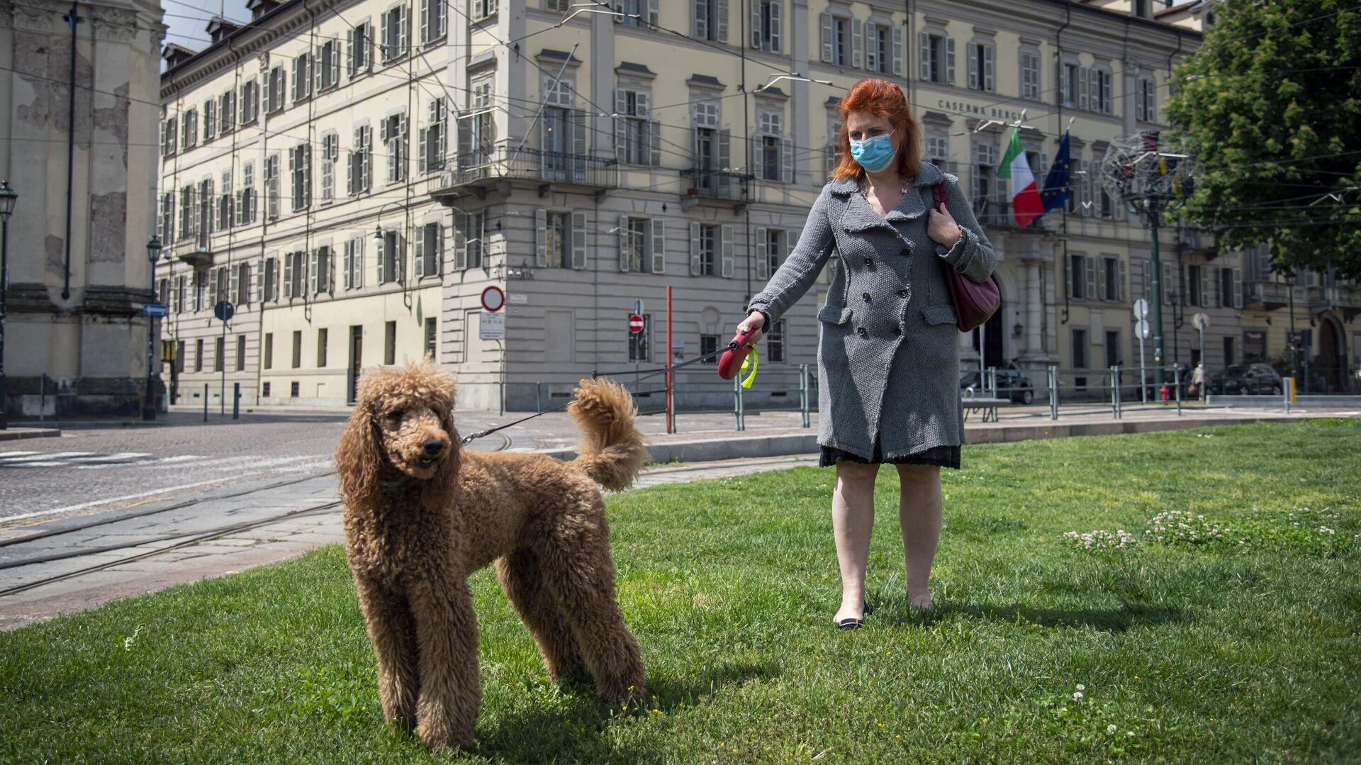 Женщина гуляет с собакой в центре города в Турине - РИА Новости, 1920, 06.11.2020