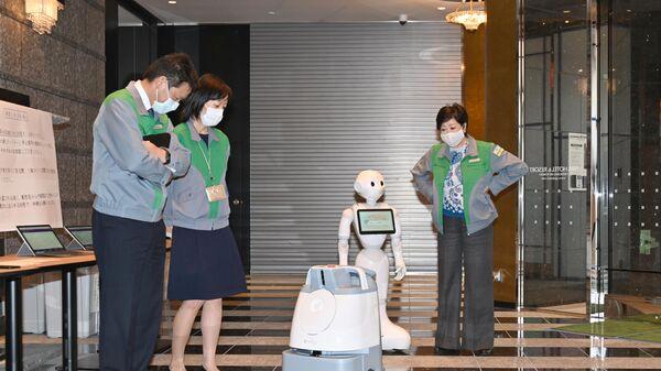 Робот, обслуживающий зараженных коронавирусом на обсервации в токийских гостиницах. Справа губернатор Токио Коикэ Юрико