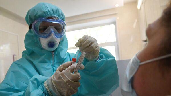 Медицинский работник в защитном костюме проводит забор биоматериала для анализа на коронавирус в городской поликлинике Москвы