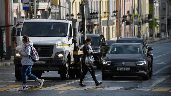 Пешеходы переходят улицу в Москве