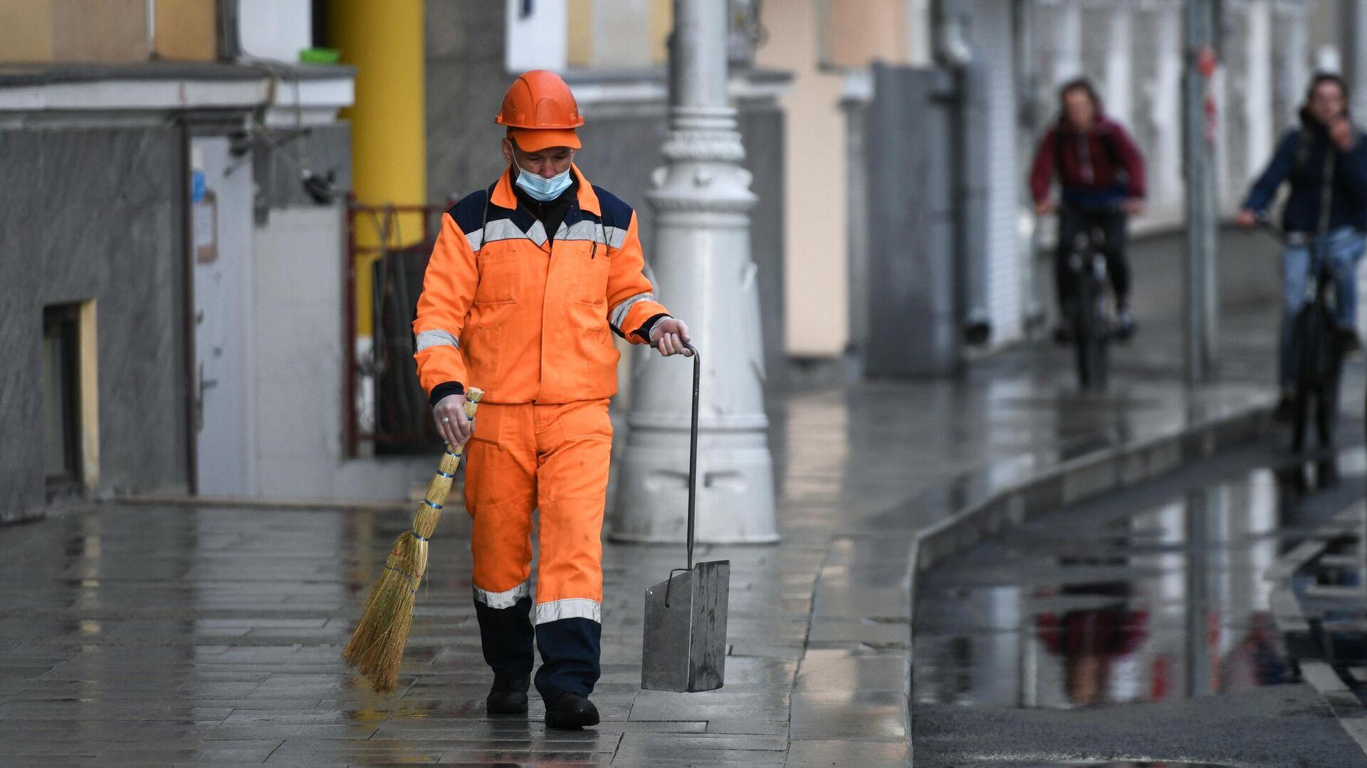 Сотрудник коммунальной службы убирает улицу в Москве - РИА Новости, 1920, 20.05.2021