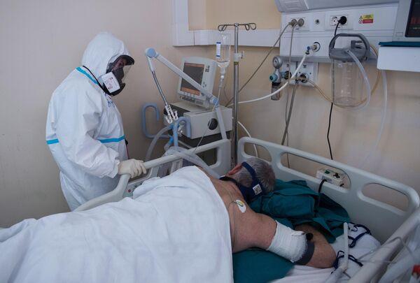 Медицинский работник возле кровати пациента в отделении реанимации и интенсивной терапии госпиталя COVID-19 в ГКБ No1 имени Н.И. Пирогова в Москве