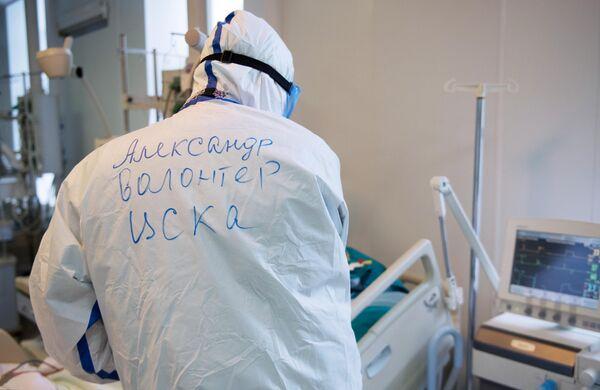 Волонтер возле кровати пациента в отделении реанимации и интенсивной терапии госпиталя COVID-19 в ГКБ No1 имени Н.И. Пирогова в Москве