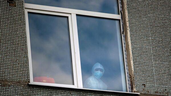 Медицинский работник в окне одной из палат Иркутской областной инфекционной больницы