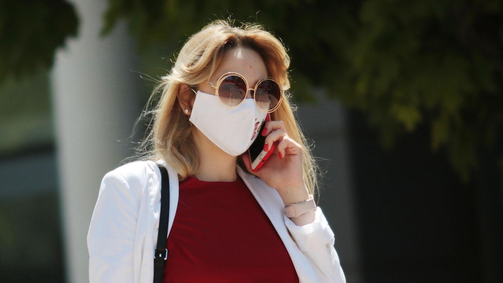 Девушка разговаривает по телефону, гуляя в защитной маске по Гагаринскому парку в Симферополе - РИА Новости, 1920, 06.05.2021