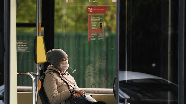 Женщина в защитной маске в салоне трамвая в Москве