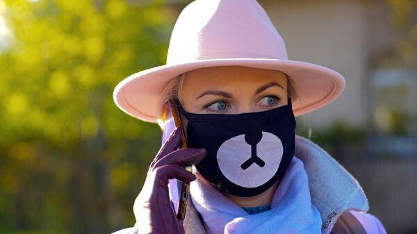 Девушка в защитной маске на одной из улиц района Жулебино в Москве