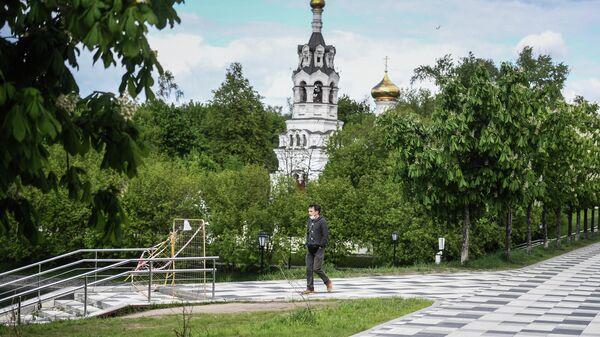 Прохожий у храма Ильи Пророка в Черкизове в Москве  во время режима самоизоляции жителей