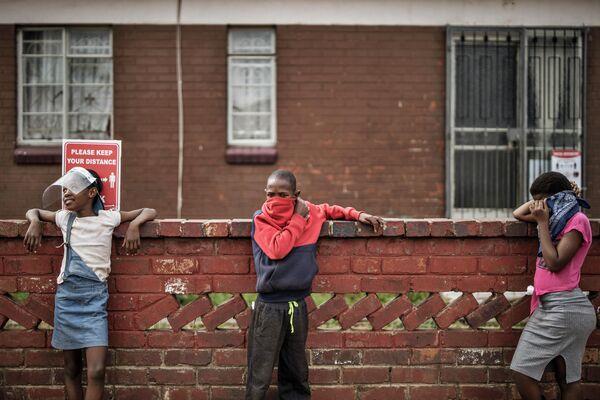 Дети стоя в очереди на раздачу продуктов питания благотворительной организацией в Уэстбери, Йоханнесбург