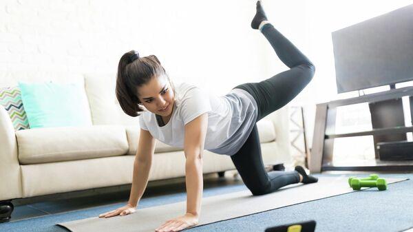 Девушка занимается фитнесом дома