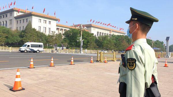 Сотрудник службы безопасности возле Дома народных собраний в Пекине