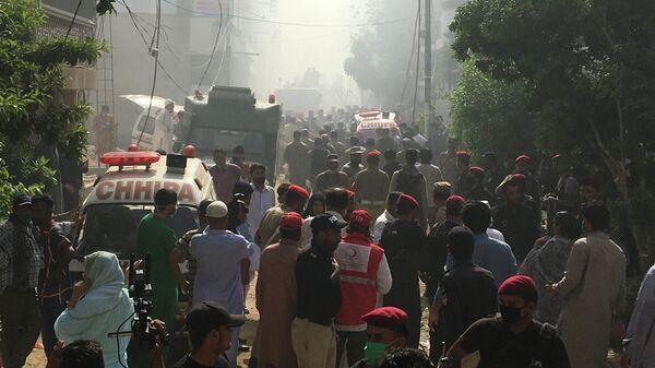 Машины скорой помощи на месте крушения пассажирского самолета в жилом районе недалеко от аэропорта в Карачи